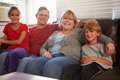 Portrait of happy family sitting on sofa together with arms around each other smiling at camera Stock Photo