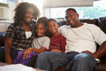 Portrait of happy family sitting on sofa together smiling at camera Royalty Free Stock Image