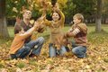Portrait of a happy family throw autumn leaves Stock Photos