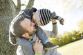 Portrait of happy father giving son piggyback ride a on his shoulders in autumn park Stock Image