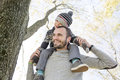 Portrait of happy father giving son piggyback ride a on his shoulders in autumn park Stock Images