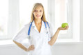 Portrait of a happy female doctor with green apple on light background Royalty Free Stock Images