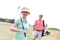 Portrait of happy female golfer with friend standing in background Royalty Free Stock Photo