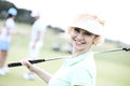 Portrait of happy female golfer holding golf club Royalty Free Stock Photo