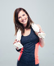 Portrait of a happy fitness woman with towel standing over gray background and looking at camera Stock Photography