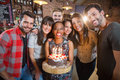 Portrait of happy friends holding birthday cake Royalty Free Stock Photo