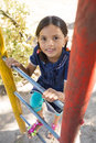 Portrait of happy girl climbing ladder of jungle gym Royalty Free Stock Photo