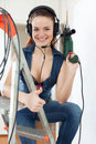 Portrait of happy girl in headphones with drill sexy on stepladder interior Stock Photography
