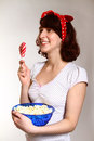 Portrait of happy girl with lollipop and popcorn watching Stock Photos