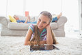 Portrait of happy girl using digital tablet on rug at home with mother reading book in background living area Royalty Free Stock Images