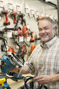Portrait of a happy hardware store owner with electric saw Stock Photo