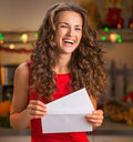 Portrait of happy housewife with christmas letter in kitchen Royalty Free Stock Photo