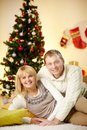 Portrait of happy husband and wife relaxing at home on christmas day Stock Image