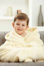 Portrait of happy kid sitting in oversize bathrobe caucasian after taking bath smiling looking at camera home indoor sofa Stock Images