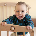 Portrait happy laughing baby standing cot Stock Images