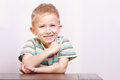 Portrait of happy laughing blond boy child kid at the table Royalty Free Stock Photo