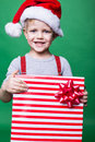 Portrait of a happy little boy holding a new christmas gift studio over green background Stock Photos