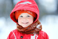 Portrait of happy little boy in red winter clothes having fun during snowfall Royalty Free Stock Photo