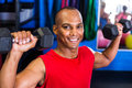 Portrait of happy man lifting dumbbell in gym Royalty Free Stock Photo