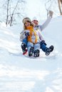 Portrait of happy mature couple riding on sledge in winter Stock Image
