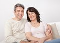 Portrait of happy mature couple sitting at home in the couch Stock Image