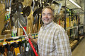 Portrait of a happy mature man holding shovel in hardware store Royalty Free Stock Photo