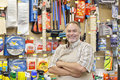 Portrait of a happy mature salesperson with arms crossed in hardware store Royalty Free Stock Images
