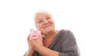 Portrait of a happy mature woman holding piggy bank isolated aga senior showing over white background Royalty Free Stock Photography