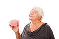 Portrait of a happy mature woman holding piggy bank isolated aga senior showing over white background Royalty Free Stock Photos
