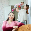 Portrait of happy mature woman women against her adult daughter holds little baby at home interior Stock Images