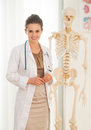 Portrait of happy medical doctor woman near human skeleton anatomical model Royalty Free Stock Photo