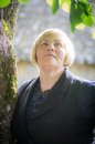 Portrait of happy middle aged woman blond close the tree Stock Photography
