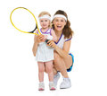 Portrait of happy mother and baby holding tennis racket isolated on white Royalty Free Stock Photography