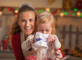 Portrait of happy mother and baby making christmas cookies in decorated kitchen Stock Photos
