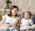 Portrait of happy mother and daughter in bed hugging and smiling talking Stock Photo