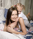 Portrait of happy mother and daughter in bed hugging and smiling talking Stock Photos