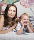 Portrait of happy mother and daughter in bed hugging and smiling talking Royalty Free Stock Photo