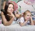 Portrait of happy mother and daughter in bed hugging and smiling talking Royalty Free Stock Photography