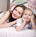 Portrait of happy mother and daughter in bed hugging and smiling talking Stock Image