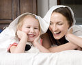 Portrait of happy mother and daughter in bed hugging and smiling talking Stock Images