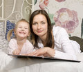 Portrait of happy mother and daughter in bed hugging and smiling talking reading book Royalty Free Stock Photo