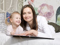 Portrait of happy mother and daughter in bed hugging and smiling talking reading book Royalty Free Stock Image