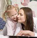 Portrait of happy mother and daughter in bed hugging and smiling talking reading book Stock Image