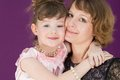 Portrait of a happy mother and daughter in a purple room the hugging Stock Image