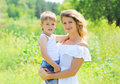 Portrait of happy mother hugging child son outdoors in summer Royalty Free Stock Photo