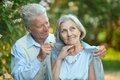 Portrait of a happy older couple on walk in the park Stock Images