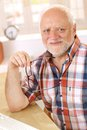 Portrait of happy older man smiling at camera holding glasses Royalty Free Stock Photo