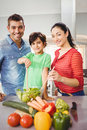 Portrait of happy parents and son preparing salad while standing at home Stock Image