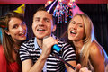 Portrait of happy people singing in microphone in the karaoke bar Stock Photo