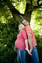 Portrait of a happy pregnant couple in jeans and pink t shirts standing back to back Royalty Free Stock Image